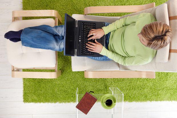 Woman sitting typing on laptop