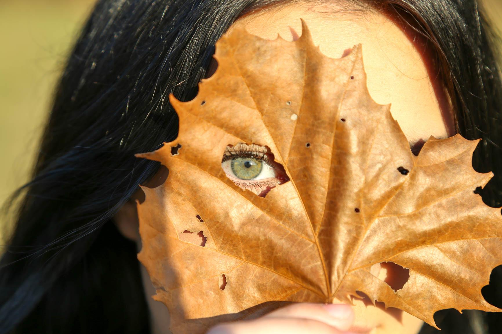 woman's face peeking through a crumpled leaf