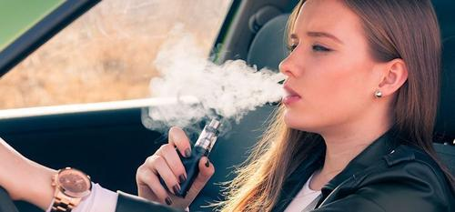 Teenaged female vaping while driving