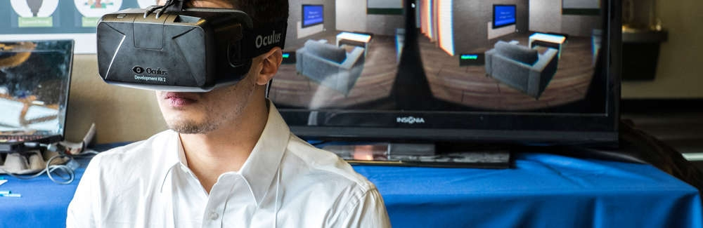 student stands in front of monitors with protosight virtual reality unit on his face
