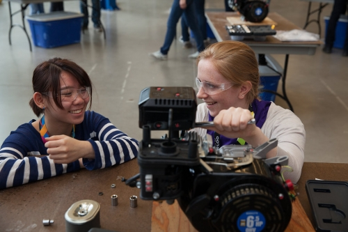 Two participants taking apart an engine