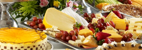 Cheese platter surrounded by cakes and fruit