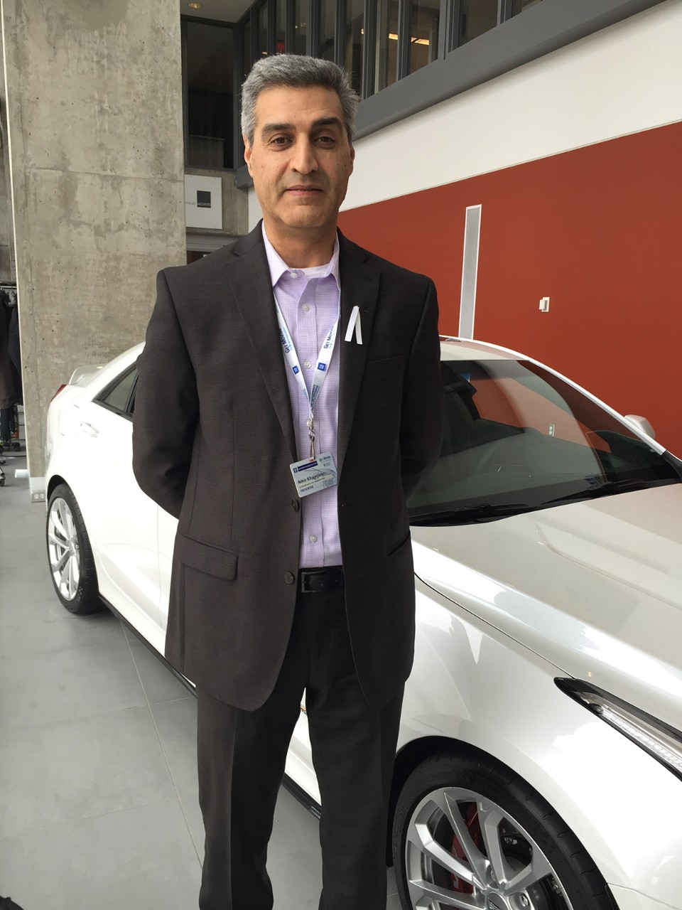 Amir Khajepour standing in front of a new white car. He is wearing a black blazer with a violet dress shirt.