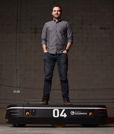 Matt Rendall, CEO and co-founder of Clearpath Robotics, stands on an OTTO 1500, the self-driving heavy load materials transporte