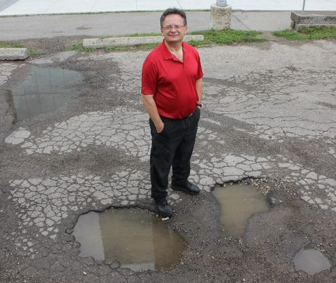 professor John Zelek beside pot holes