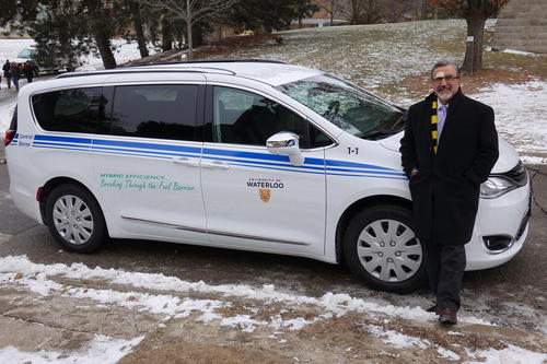 President Feridun Hamdullahpur stands next to the Central Stores hybrid service vehicle.