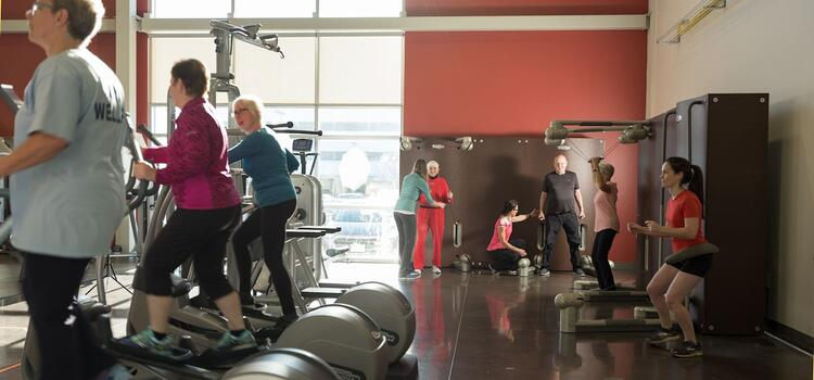 Clients working out on treadmills and exercise equipment in CCCARE gym.