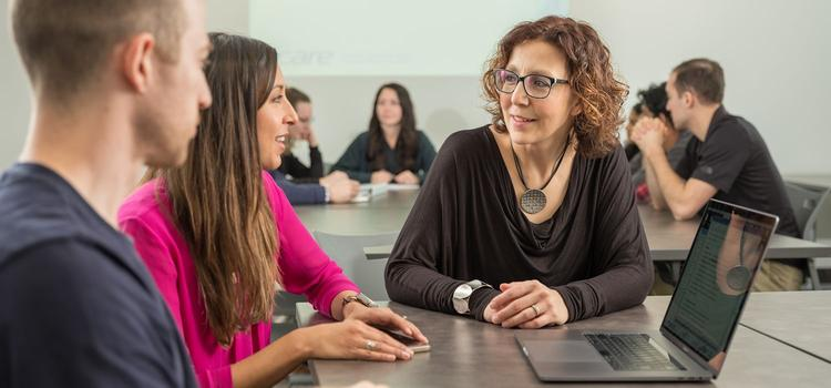 Professor Marina Mourtzakis talking to students in front of laptop computer.