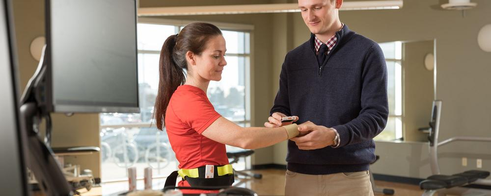 Researcher applying wearable device on participant.
