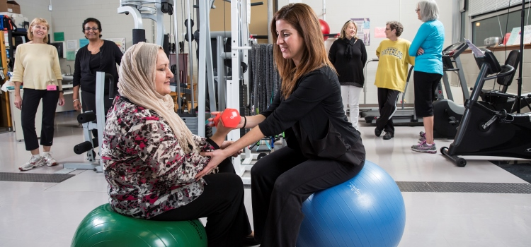 Trainer working with Living Fit client in gym.