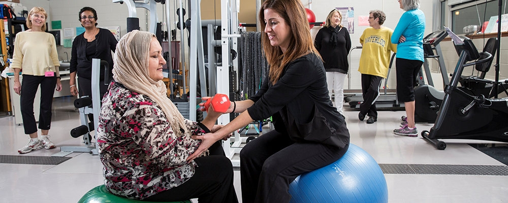 Women helping another women exercise with free weight.