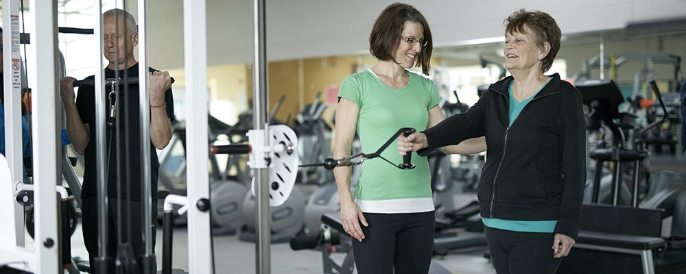 Client performing exercise with trainer helping