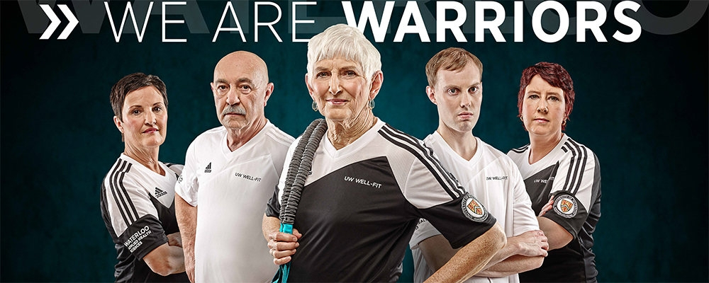 Five well-fit participants in team uniform with We Are Warriors slogan.