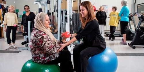 Woman assisting another woman with free weights.