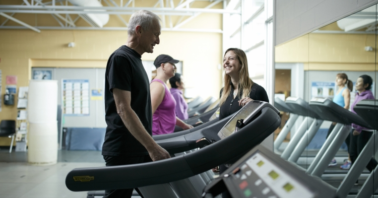 Volunteer talking with UW WELL-FIT participant on the treadmill