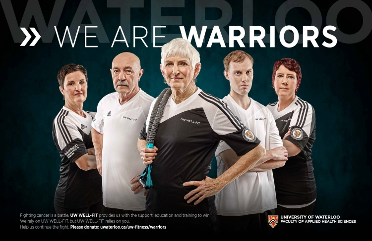 Well-fit participants stand under we are warriors banner.