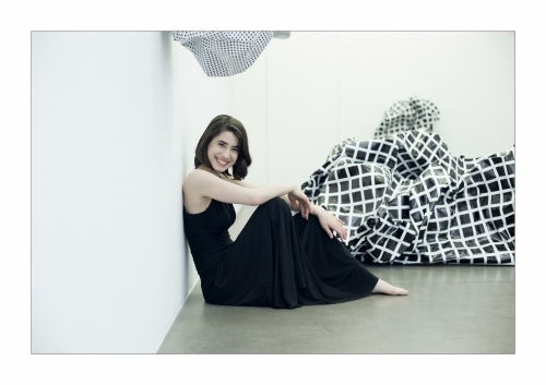 Photo of Austrian pianist Ann Magdalena Kokits in a black dress, sitting on the floor.