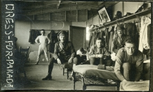 Several WWI soldiers in barracks getting dressed.