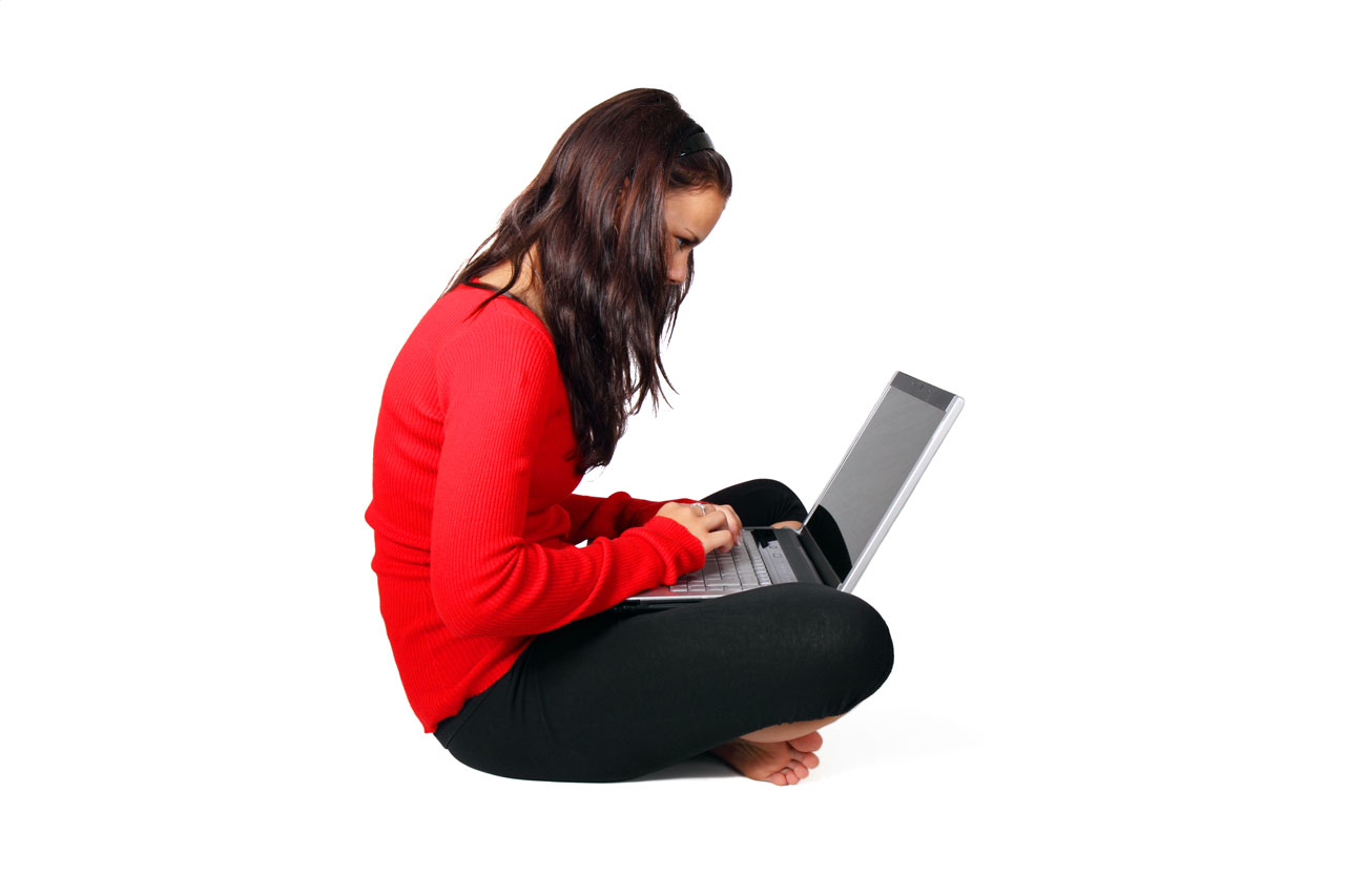 Profile view of young woman in a red shirt and black pants sitting on the floor, with a laptop in her lap.