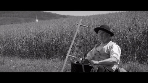 19th-century farmer sitting in front of some fields.