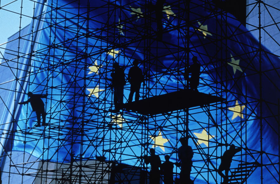 Scaffolding and men in shadow, in front of a very large EU flag