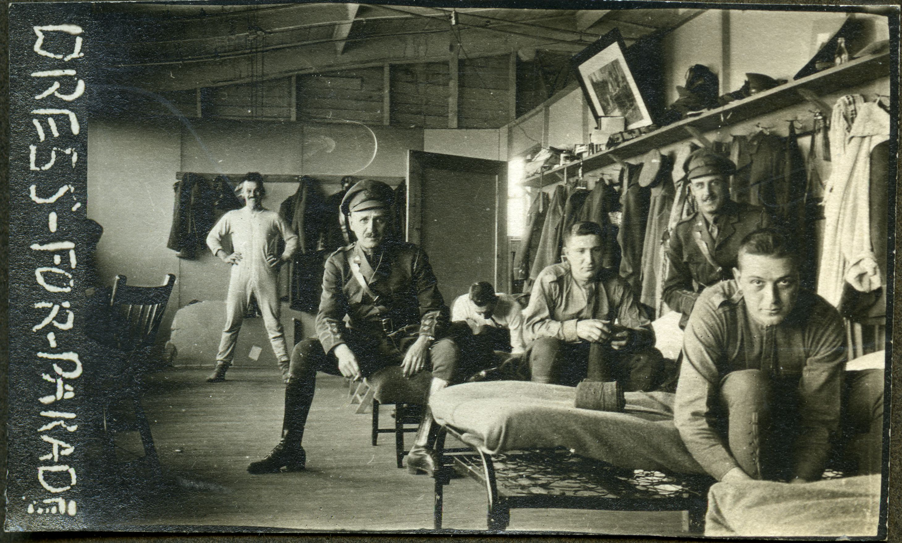 Barracks in Kitchener, with men getting dressed into military uniforms, 1910s.
