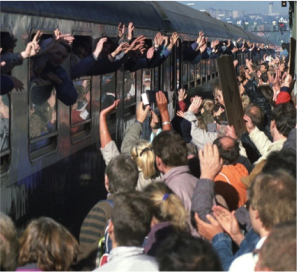 Train with lots of people waving out of partially closed windows. Many people on train platform waving.