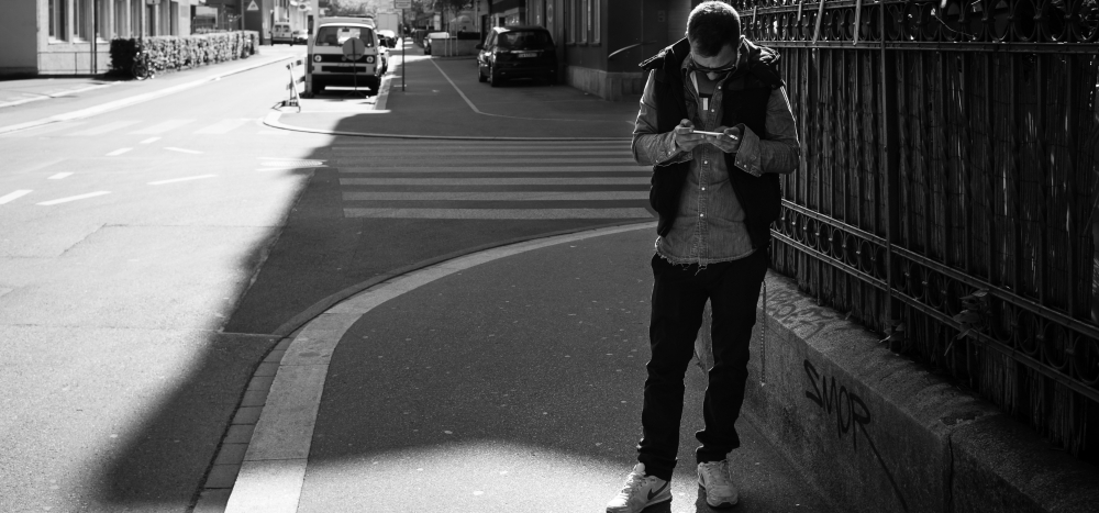 A man standing on a sidewalk focused on his smartphone.