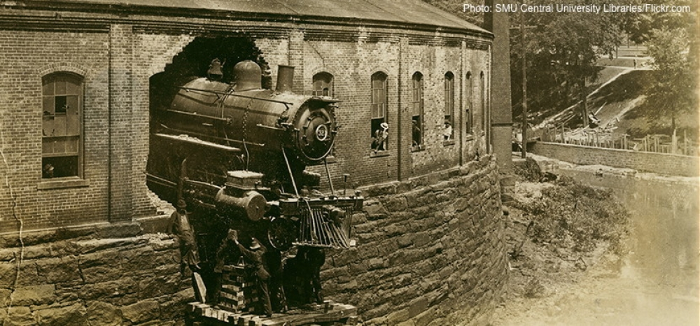 A locomotive has crashed through the back wall of a railroad roundhouse.
