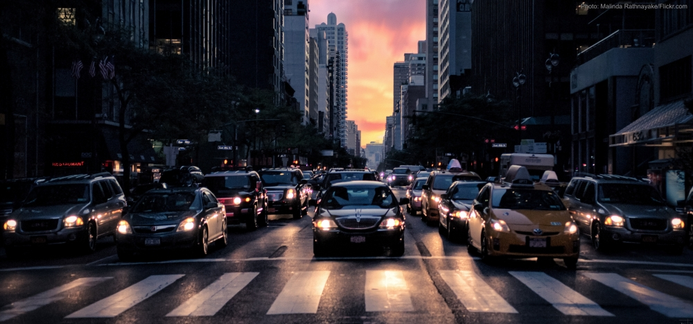 Cars wait to advance through an intersection in New York City at dusk.