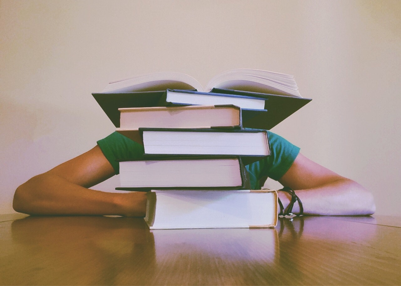 Student slumped behind a stack of books