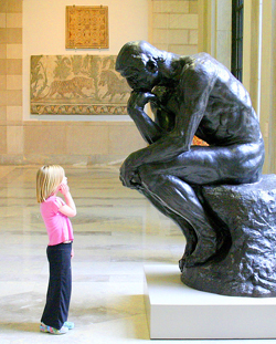 Photo of a child looking at Rodin's The Thinker