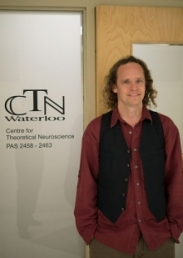 Chris Eliasmith standing in front of the Centre for Theoretical Neuroscience office door