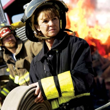 Female firefighter carries fire hose.