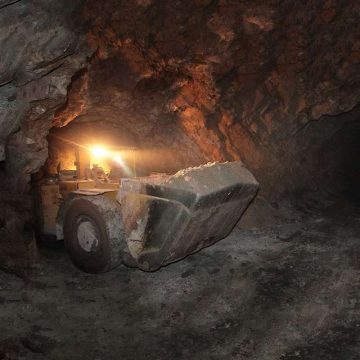 Loader carrying rock in mine.