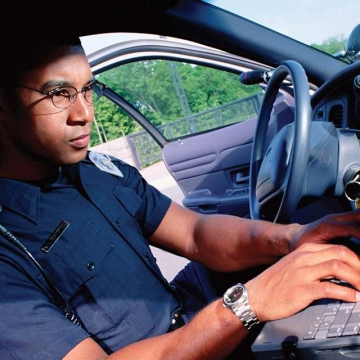 Police types on keyboard in cruiser.