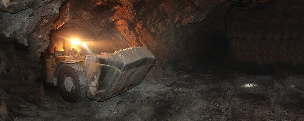 Mining construction vehicle exits underground tunnel in mine.
