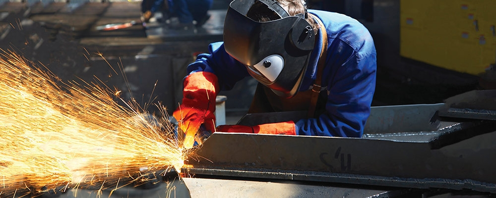 Worker wearing welding helmet and gloves welds metal while sparks fly.