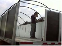 Man using rack and tarp kit to install tarp