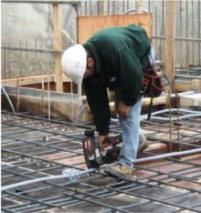 Worker tying conduit to rebar using a mechanical tying tool