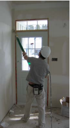 Worker finishing drywall using pneumatic drywall finishing system