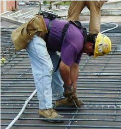 Worker tying rebar by hand