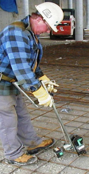 Worker using rebar-tying tool with extension