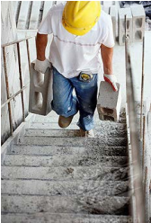 Worker manually transporting materials up stairs
