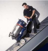 Worker using a stair climbing hand truck