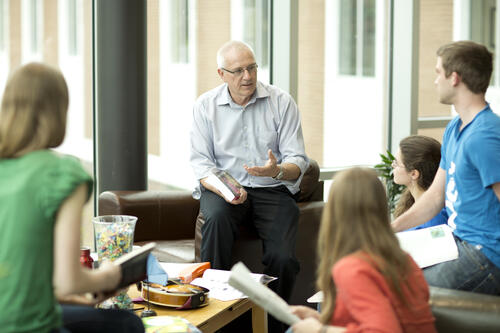 Lowell Ewert speaking with a group of students at Conrad Grebel
