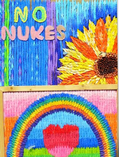"""Painted wall mural with sunflower and rainbow saying """"no nukes"""""""