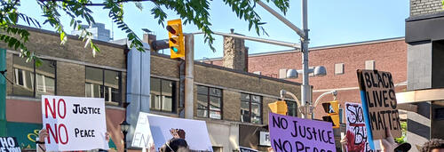 """Protesters display colourful signs saying """"no justice, no peace"""" and """"Black lives matter"""" while standing outside of Grebell"""