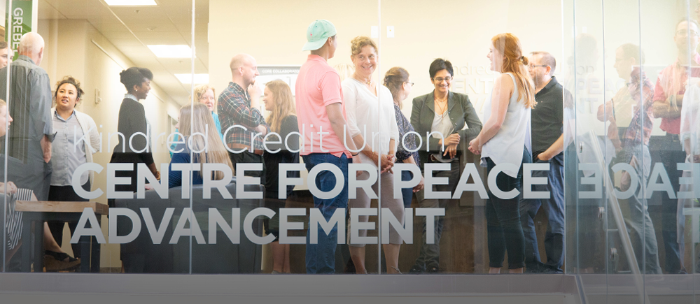 People stand in conversation with one another behind the front windows of the Centre for Peace Advancement