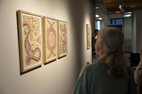A woman looking at the art work
